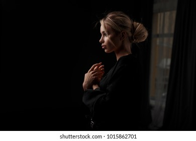 Beautiful young woman in stylish black clothes posing in a dark room