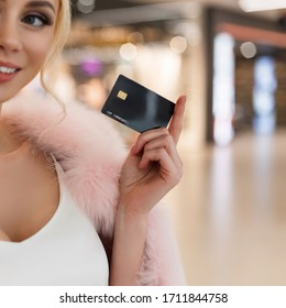 Beautiful young woman in stylish elegant luxurious fur coat holds credit card. Fashionable beautiful girl came to the store for shopping. Shopping time. Close-up.