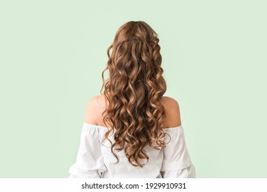 Beautiful young woman with stylish hairdo on color background, back view - Shutterstock ID 1929910931