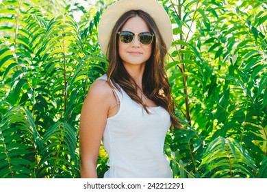 Beautiful young woman in stylish hat and jeans shorts posing. Hipster style. Summer time