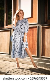 Beautiful young woman in stylish light blue polka dot dress with handbag on city street