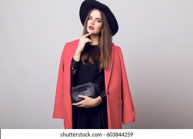 Beautiful young woman in stylish spring pink coat and black hat posing in studio, holding in hands black purse ,  looking at camera. cold season. Autumn or winter look.