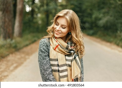 Beautiful young woman in a stylish vintage scarf walks in the park in autumn day.