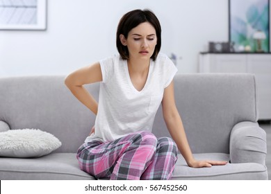Beautiful young woman suffering from backache at home