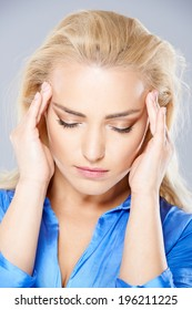 Beautiful young woman suffering from a headache rubbing her temples with her fingers and closing her eyes in pain  closeup head and shoulders