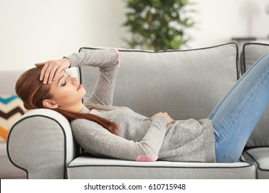 Beautiful young woman suffering from headache at home