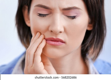 Beautiful young woman suffering from toothache, close up
