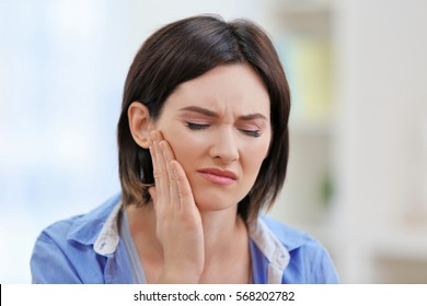 Beautiful young woman suffering from toothache at home
