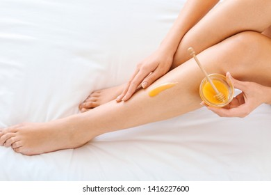 Beautiful young woman with sugaring paste epilating legs at home