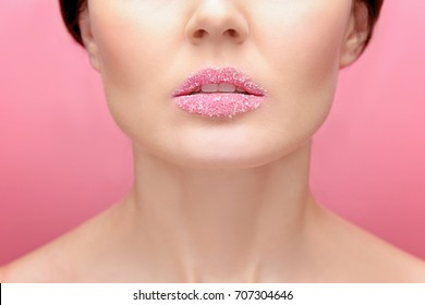 Beautiful young woman with sugary lips on color background