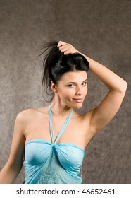 The beautiful, young woman in a summer dress of blue color.