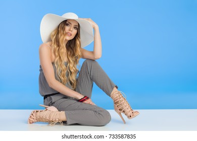 Beautiful young woman in summer jumpsuit, high heels and white sun hat is sitting on floor and looking at camera. Full length studio shot.