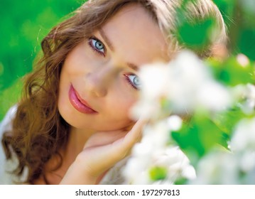 beautiful young woman in the summer park, near the apple tree with flowers