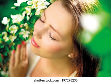 beautiful young woman in the summer park, standing near the apple tree with flowers