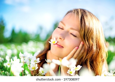 beautiful young woman in the summer park, lying on the grass with flowers