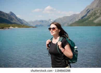 beautiful young woman in sunglasses with backpack standing near majestic Gjende lake, Besseggen ridge, Jotunheimen National Park, Norway