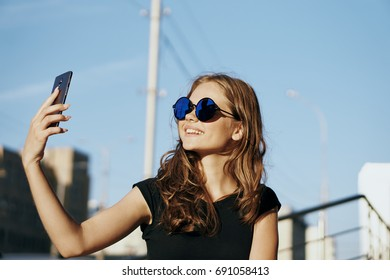 Beautiful young woman in sunglasses doing selfie outdoors in the city.