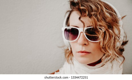 Beautiful young woman in a sunglasses and headphones listening to music standing at the wall. Casual style concept.