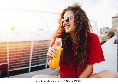 Beautiful young woman in sunglasses holds a bottle with fresh juice, looking away, sitting on marble slab in a sunny day, outdoors.
