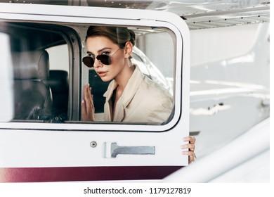 beautiful young woman in sunglasses and jacket looking at camera near aircraft