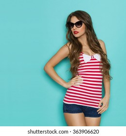 Beautiful young woman in sunglasses and red striped shirt with white bow posing with hand on hip and looking away. Three quarter length studio shot on teal background.