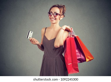 Beautiful young woman in sunglasses with shoppping bags and credit card smiling