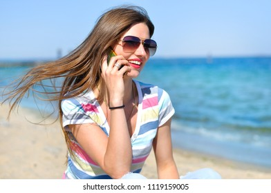 Beautiful young woman in sunglasses sits at the sea shore in the sand with a cup of coffee and speaks on the phone