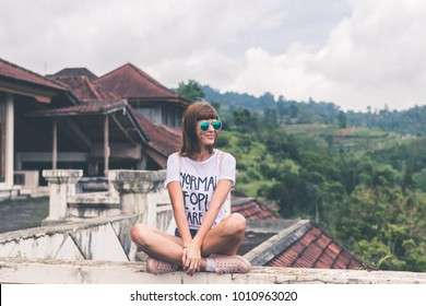 Beautiful young woman in sunglasses sitting on tropical jungle background. Bali island, Indonesia. Asia.