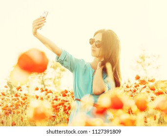 Beautiful young woman in sunglasses taking selfie with smartphone in poppies meadow on sunny summer day.