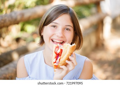 Beautiful young woman with sunny smile eating juicy burger . Close-up of fast food on the nature background.