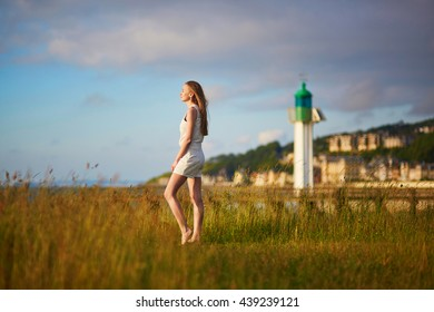 Beautiful young woman at sunset on meadow near lighthouse in Deaville, Normandy, Northern France, Europe