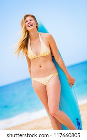 Beautiful Young Woman Surfer Girl in Bikini with Surfboard at a Beach