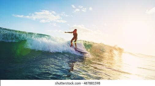 Schöne junge Frau, die bei Sonnenuntergang surfen