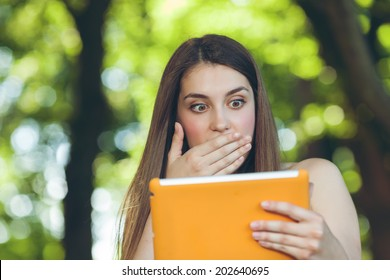 Beautiful young woman surprised and worried sitting on the bench in park getting bad news on tablet.