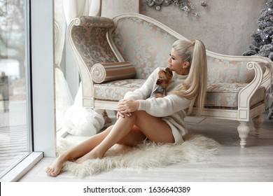 beautiful young woman in sweater with little dog, cozy home