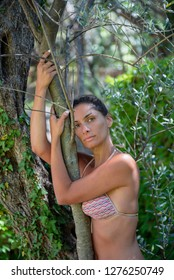 Beautiful, young woman in swim suit posing in nature, leaning on tree. Concept: healthy life, self care, spring resolution, recreation, new beginning, meditation, self love, nature lover, harmony