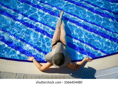 beautiful young woman in the swimming pool on a sunny summer day, view from above