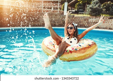 Beautiful young woman in swimming pool swims on inflatable ring donut and has fun in water on vacation.