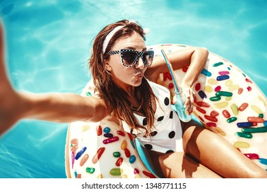 Beautiful young woman in swimming pool swims on inflatable ring donut and has fun with glass of cocktail on vacation.