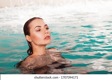 Beautiful young woman swimming in the pool, portrait. Attractive brunette girl enjoys relaxation in the water.