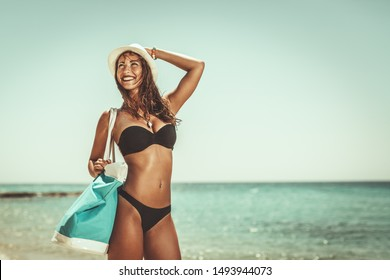 Beautiful young woman in swimsuit is enjoying at sunbathing on the beach.