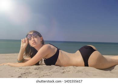 beautiful young woman in swimsuit at sand sea beach under light rays sunbathes