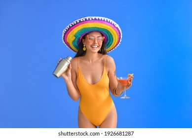 Beautiful young woman in swimsuit, sombrero hat and with cocktail against color background