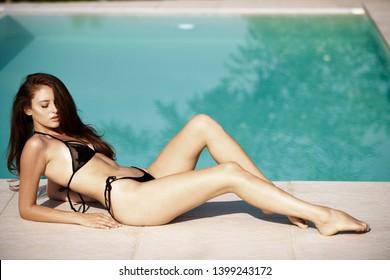 Beautiful young woman in swimsuit sunbathing near pool  .