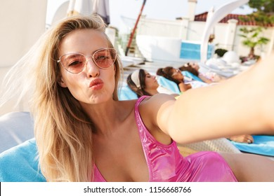 Beautiful young woman in swimsuit, sunglasses taking a selfie while spending good time a swimming pool resort