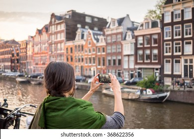 beautiful young woman takes pictures in vacation spent in Amsterdam with beautiful architecture