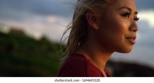Beautiful young woman takes in a sunset while on vacation as her hair is blown by the wind and ocean breeze