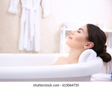 Beautiful young woman taking bath at home