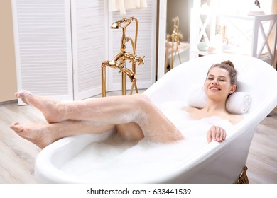 Beautiful young woman taking bath at home