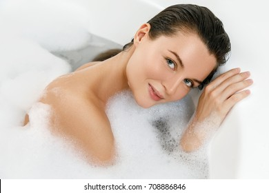 Beautiful young woman is taking bath with a pleasure